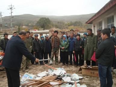 (图为通渭县法院双联人员向农户发放锄头和铁锨)-真诚双联 精准扶贫